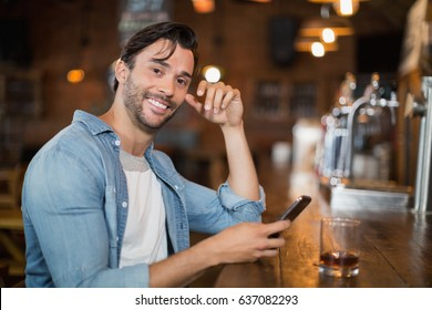 Portrait of young man using mobile while sitting at pub