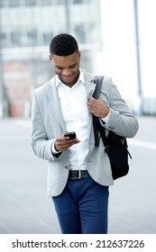 Portrait of a young man walking and looking at mobile phone