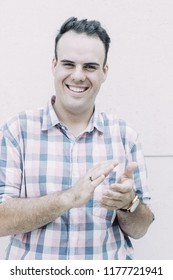 Portrait of young man wearing checked shirt standing at wall, clapping hands, looking at camera and smiling. Approval and congratulation concept