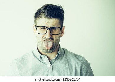 Portrait of young man wearing glasses sticking out tongue. Caucasian businessman wearing blue shirt grimacing at camera. Fun and mischief concept