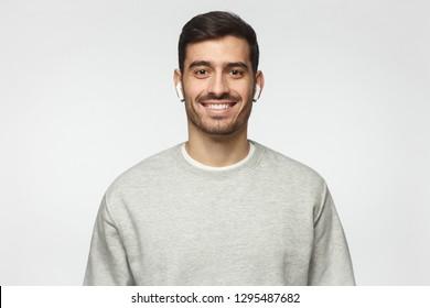 Portrait of young man wearing gray sweatshirt and earphones, isolated on gray background
