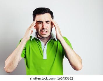 Portrait of young man wearing green shirt having head pain.Grey background.