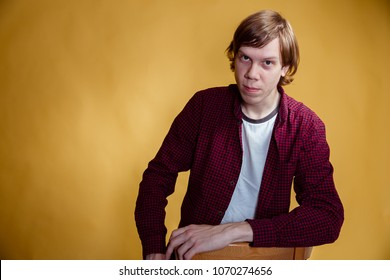 Portrait of young man wearing purple shirt and jeans over yellow background