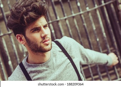 Portrait of young man wearing suspenders in urban background