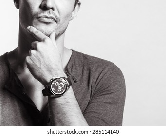 Portrait of young man wearing a watch in deep thought
