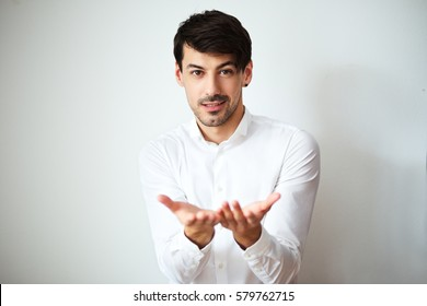 portrait of young man in white shirt stading next to color background in photostudio