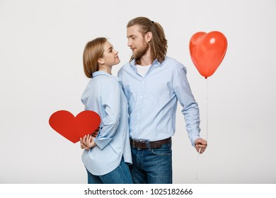 Portrait of young man and woman holding a heart- shaped balloon and paper