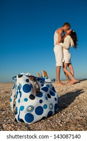 Portrait of young man and woman kissing on a beach. (Focus is on beach  bag)
