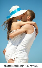 Portrait of young man and woman kissing as a happy romantic couple on a beach.