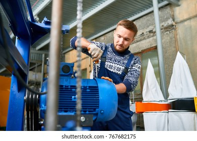 Portrait of  young man working at modern factory repairing machine units in industrial workshop, copy space