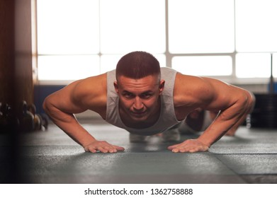 Portrait of Young Man Working Out in Gym. Young Athlete Doing Push Ups. Strength Training for Strong and Healthy Body