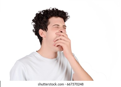 Portrait of a young man yawning. Isolated white background.