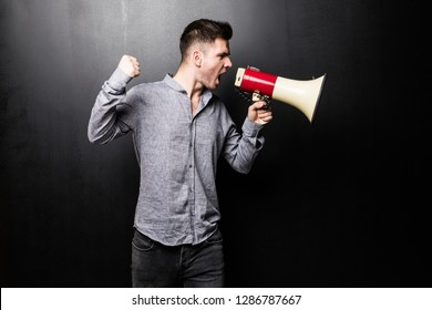 Portrait of young man yelling into the megaphone over black background