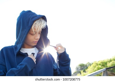 Portrait of a young man zipping up his hood sweatshirt against a sky sun flare light, thoughtful in nature outdoors on a sunny day. Teenager male relaxing in park exterior, calm and serene, exterior.