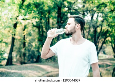 portrait of a young and masculine man drinking a water in park