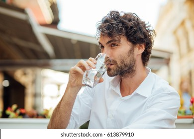 portrait of a young and masculine man drinking a water outside