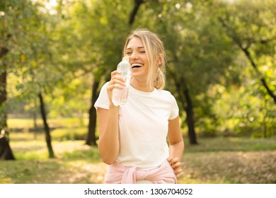 portrait of a young and masculine woman drinking a water in park after exercies in morning