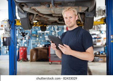 Portrait of young mechanic holding digital tablet in his auto repair shop
