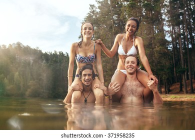 Portrait of young  men carrying their girlfriends on shoulders. Happy young couples enjoying a day at the lake.