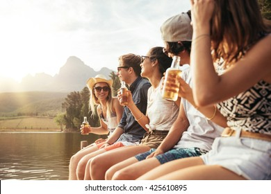 Portrait of young men and woman sitting on jetty with beers. Young men and woman enjoying a day at the lake.