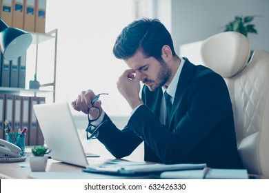 Portrait of young minded overworked student  holding his glasses and touching nose-bridge while sitting at the table