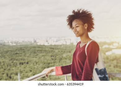 Portrait of young mixed Brazilian teen girl with curly afro hair standing on very high balcony and looking down on city district, sunny summer cityscape below with green park in blurred background