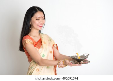 Portrait of young mixed race Indian Chinese female in traditional sari dress, holding oil lamp, on plain background.