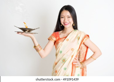 Portrait of young mixed race Indian Chinese female in traditional sari dress, holding diya oil lamp light, on plain background.