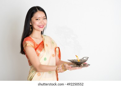 Portrait of young mixed race Indian Chinese female in traditional sari dress, holding diya oil lamp, on plain background.