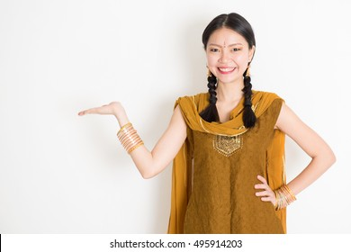 55f7c16be Portrait of young mixed race Indian Chinese female in traditional punjabi dress  hand holding somethings,