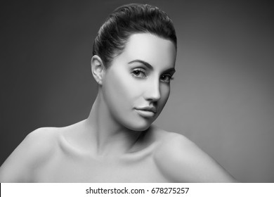 Portrait of young model girl with natural make-up, clean skin and brown hair over dark background. Black and white