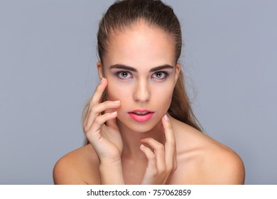Portrait of a young model, with hands at face, beauty concept, cosmetics