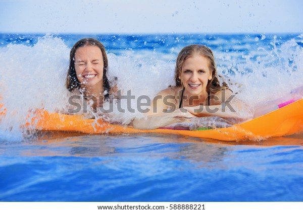 Portrait of young models on the beach in europe in summer. Two friends are swimming in sea.
