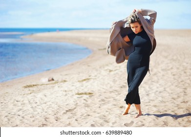 Portrait of young modern girl model in black dress and gray elegant coat, posing barefoot on a sandy beach on the seafront on a Sunny day.