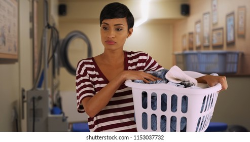 Portrait of young mom doing laundry at laundromat