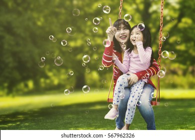 Portrait of young mother and cute child sitting on the swing while pointing at soap bubbles in the air