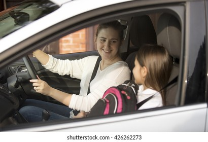 Portrait of young mother driving her daughter to school at morning