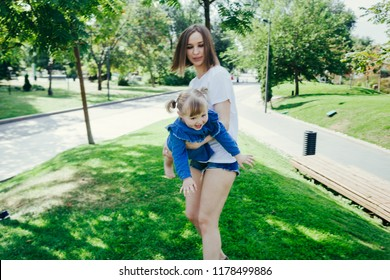 Portrait of a young mother and her 3 years old daughter playing in a city park on a warm sunny day