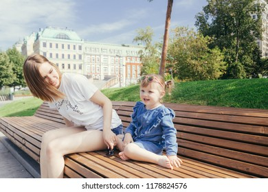 Portrait of a young mother and her 3 years old daughter sitting on the bench in a city park on a warm sunny day