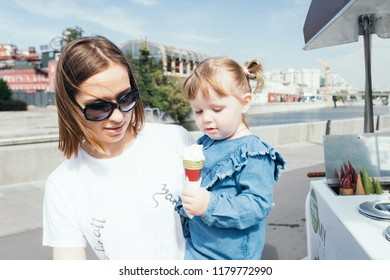 Portrait of a young mother and her 3 years old daughter eating ice cream in a city park on a warm sunny day