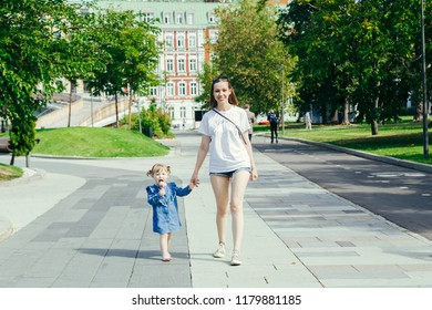 Portrait of a young mother and her 3 years old daughter walking in a city park on a warm sunny day