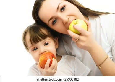 portrait of a young mother and her little daughter eating apples