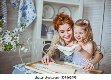 Portrait of a young mother with her little daughter sculpt a dough on a kitchen. Their noses is dirty at a flour