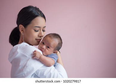 Portrait young mother holding her newborn child. Mom nursing baby. mom and baby boy relax at home. Nursery interior. Mother breast feeding baby. Family at home. Mom's love.