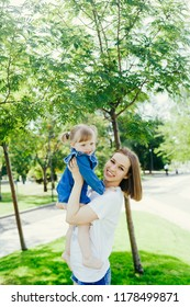 Portrait of a young mother holding her daughter in her arms smiling and looking at camera on a warm sunny day