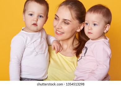 Portrait of young mother holding her little twins, cute active infants being interested to be photografed, look asides, mother looks with love on her adorable daughters. happy family concept.