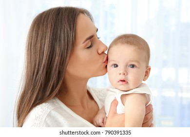 Portrait of young mother kissing cute baby at home