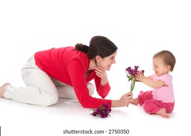 Portrait of a young mother and little baby girl sharing a new experience, a bouquet of purple flowers.
