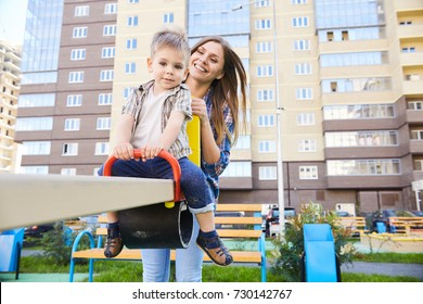 Portrait of young mother playing with cute little boy outdoors, swinging on modern playground in front of apartment building
