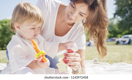 Portrait of young mother playing with her young child outdoors in the sunlight